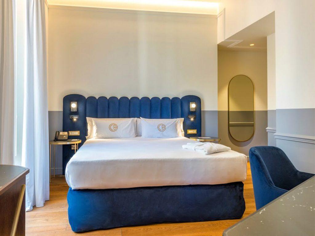 cama de hotel y butaca de terciopelo
