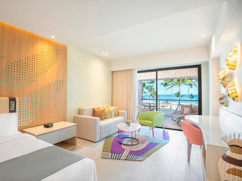 habitacion hotel cama con cabecero amarillo y decoracion butaca y sofa junto a ventana con vistas a playa en Hotel Hyatt, Zilara y Ziva con muebles de Beltá Frajumar