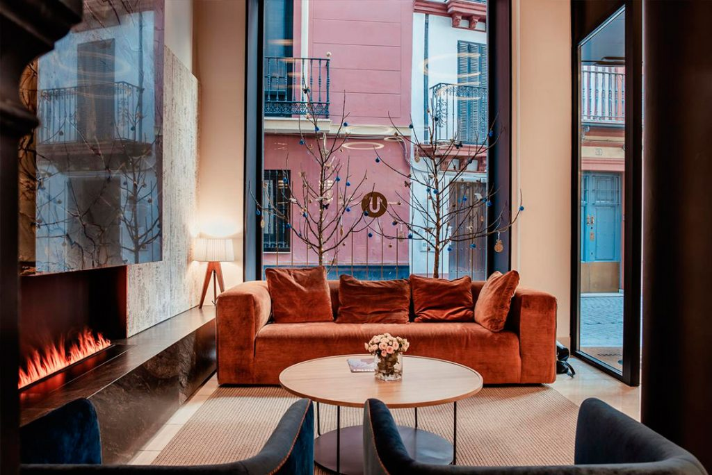Sofa marron junto a ventana en el hotel Unuk Sevilla