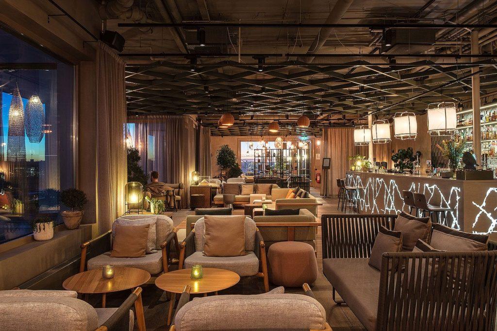 hall lounge diseño mesas de madera con sillones acogedor iluminacion lamparas y plantas de decoracion beltá frajumar