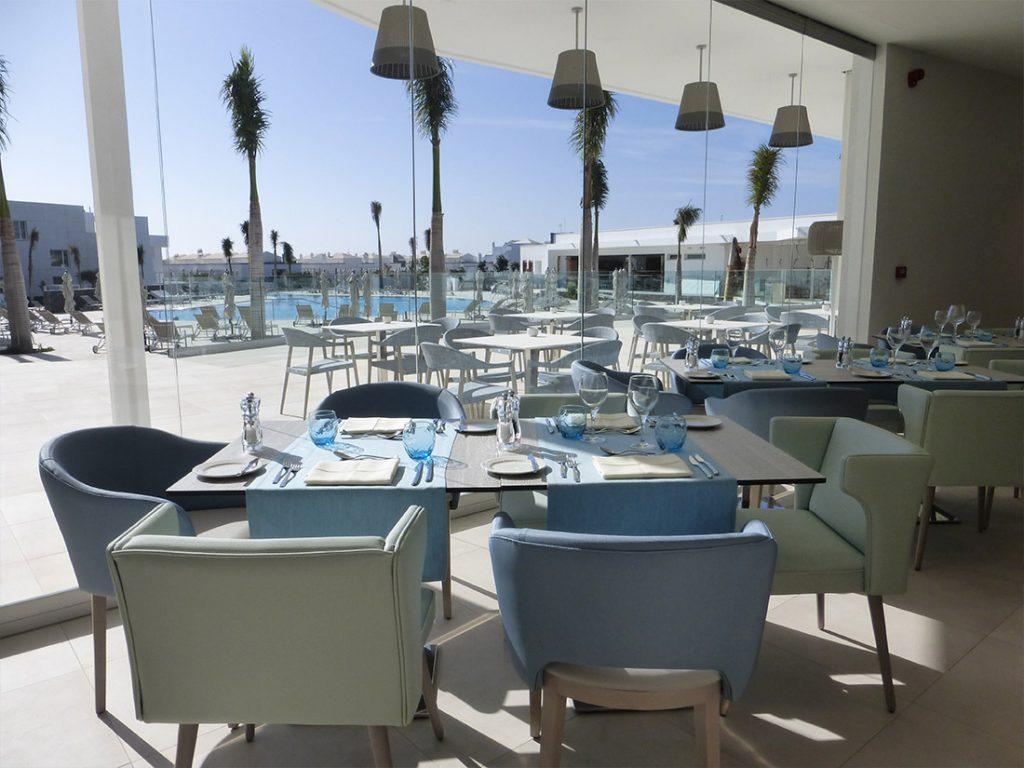 salon frente a piscina con palmeras con decoracion butacas y mesa Beltá Frajumar en hotel Lava Beach Lanzarote